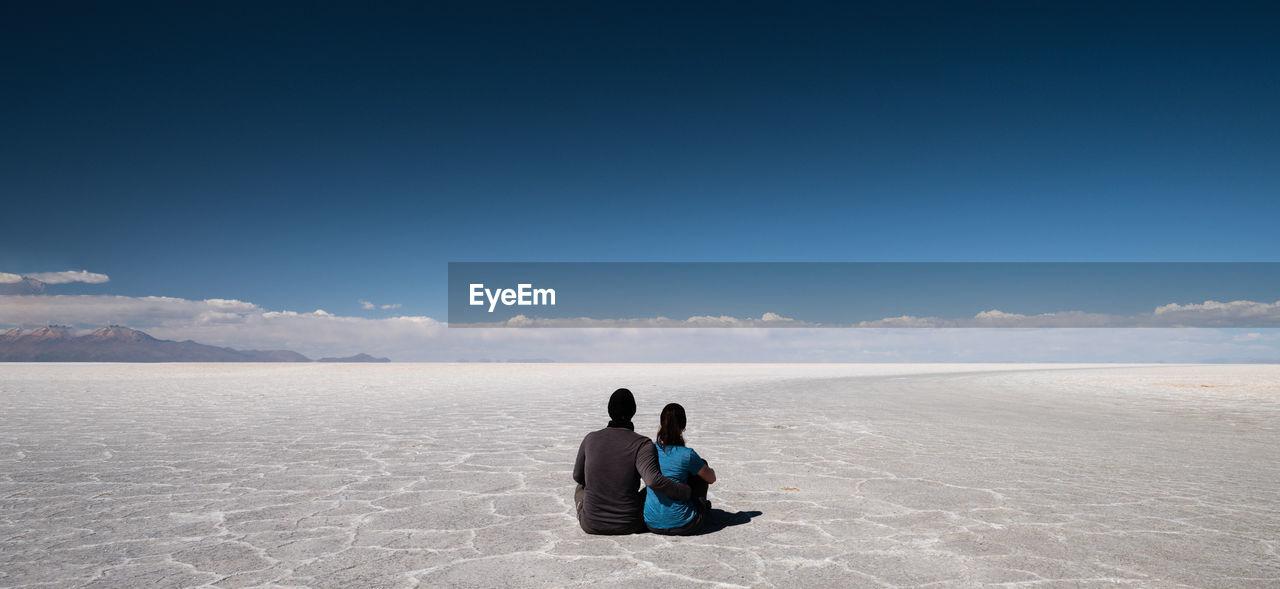 Couple Sitting On Desert Against Blue Sky