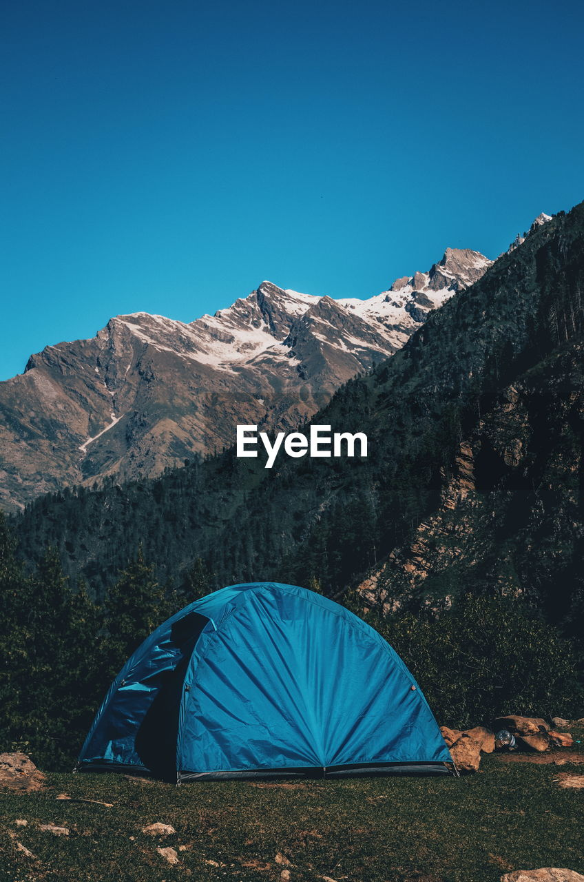 Tent In Mountains Against Clear Blue Sky