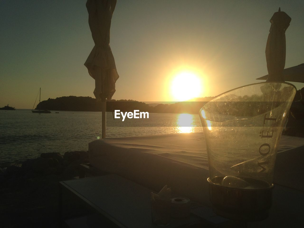 sunset, sun, sea, sunlight, water, beauty in nature, nature, scenics, outdoors, sky, drink, vacations, silhouette, no people, alcohol, clear sky, nautical vessel, close-up, day