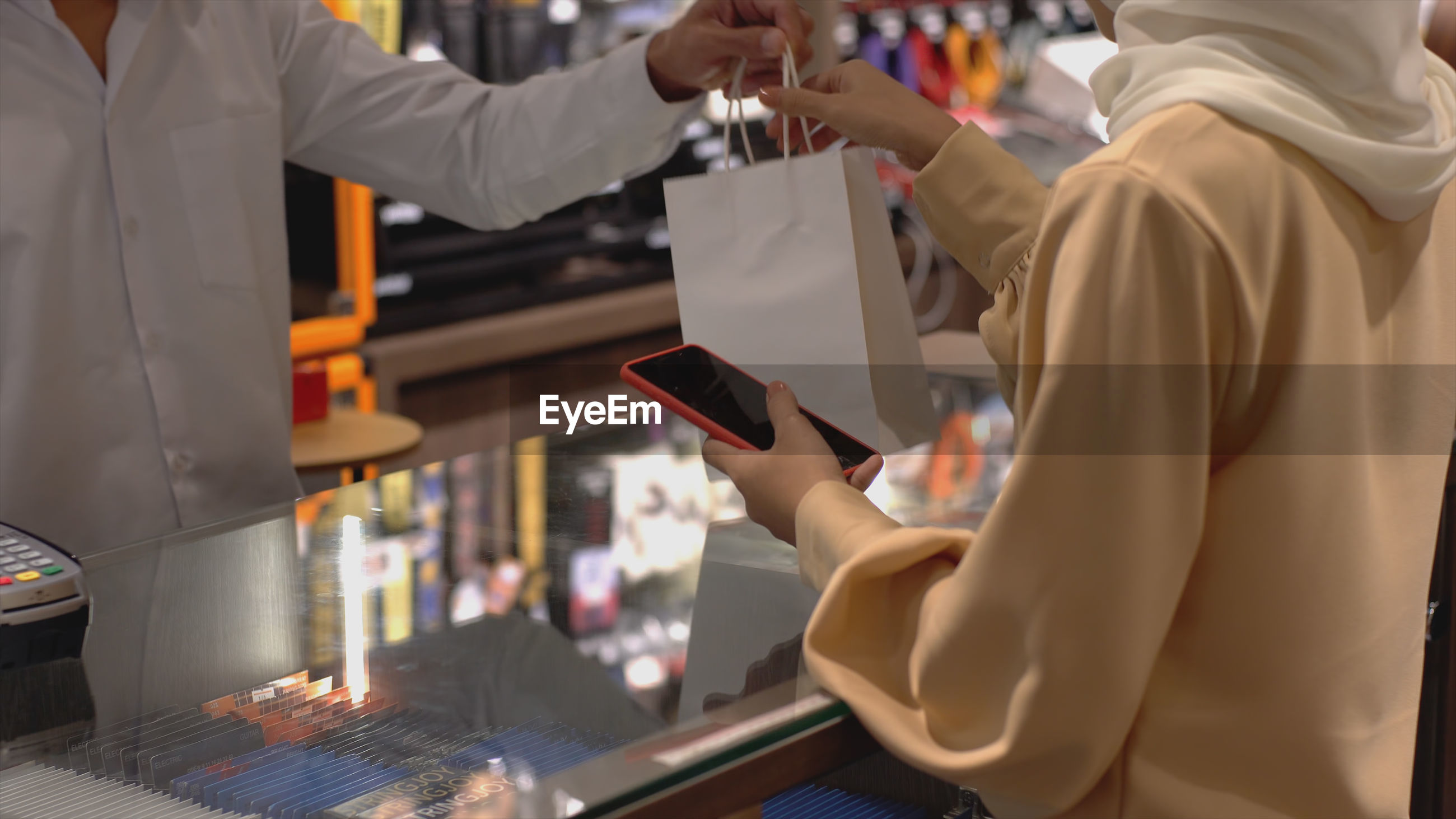 An upwardly mobile asian muslim woman using a mobile phone - smartwatch to pay for a product