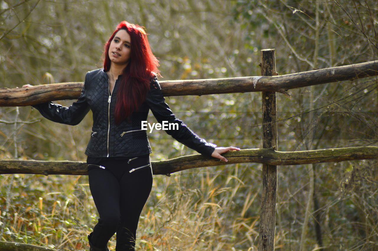 Beautiful redhead woman standing against wooden railing