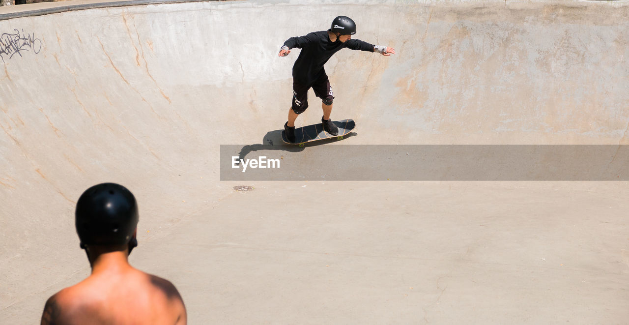 one person, full length, rear view, leisure activity, men, sport, real people, skateboard park, skateboard, lifestyles, sports equipment, boys, day, high angle view, balance, skill, childhood, risk, human body part