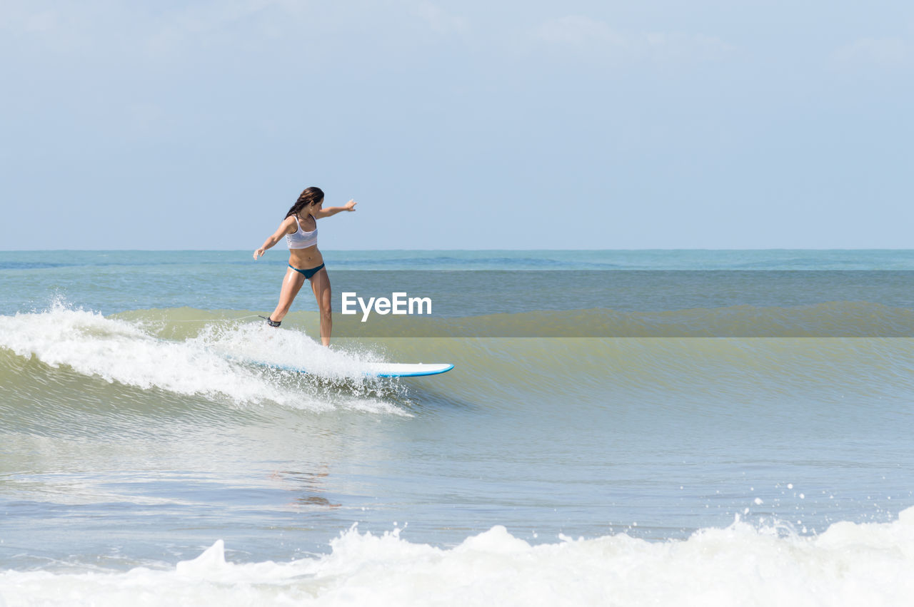Young woman surfboarding in sea