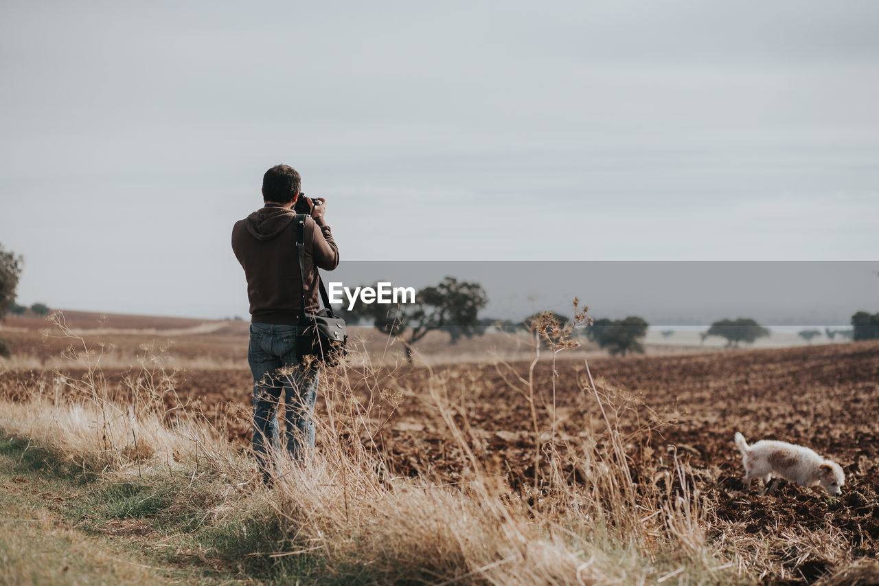 Rear view of man photographing while standing at farm against sky