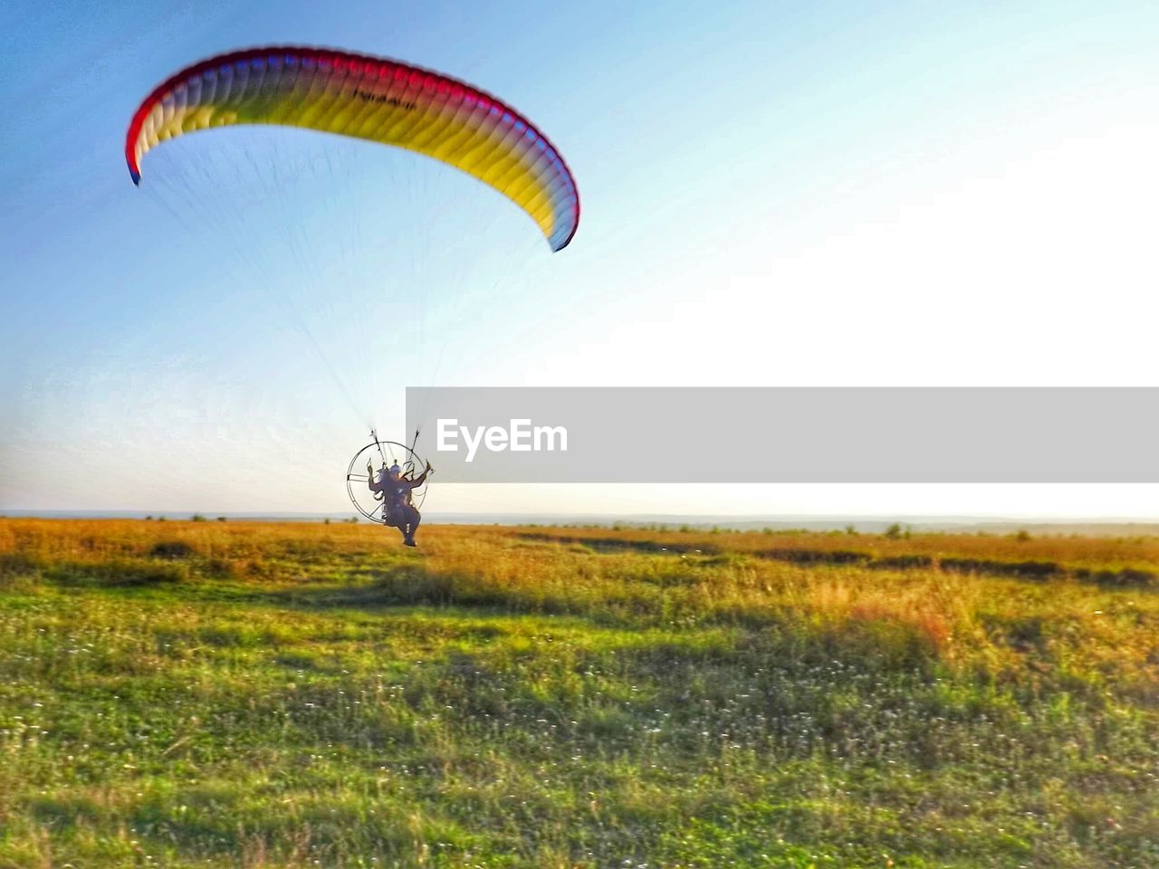 Man flying powered parachute over grassy field against clear sky