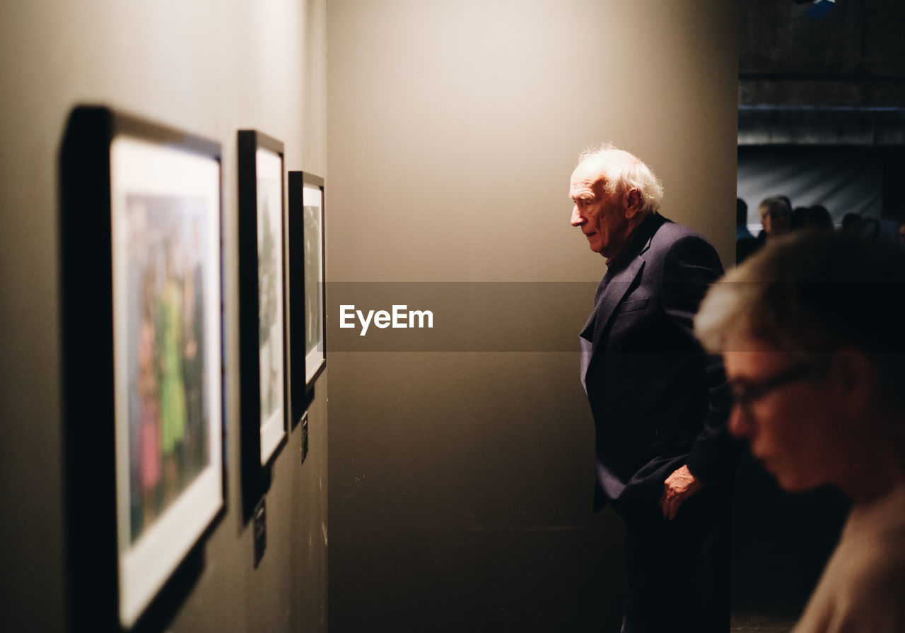 men, real people, indoors, adult, two people, males, standing, women, business, senior men, senior adult, looking, people, illuminated, selective focus, lifestyles, leisure activity, mature men, communication