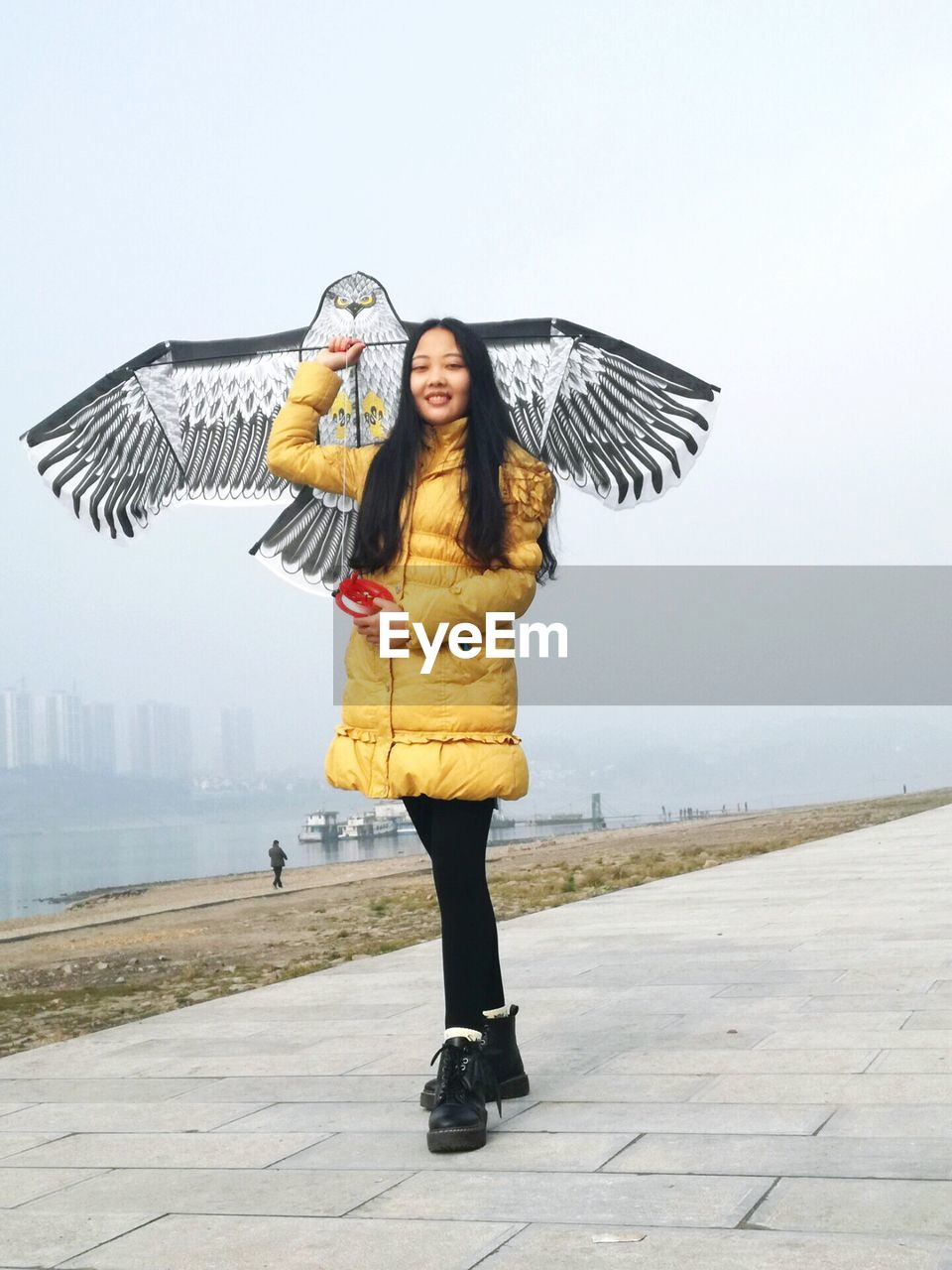 young adult, young women, real people, full length, outdoors, bird, day, casual clothing, flying, one person, animals in the wild, spread wings, leisure activity, lifestyles, animal themes, front view, happiness, one animal, smiling, beautiful woman, warm clothing, nature