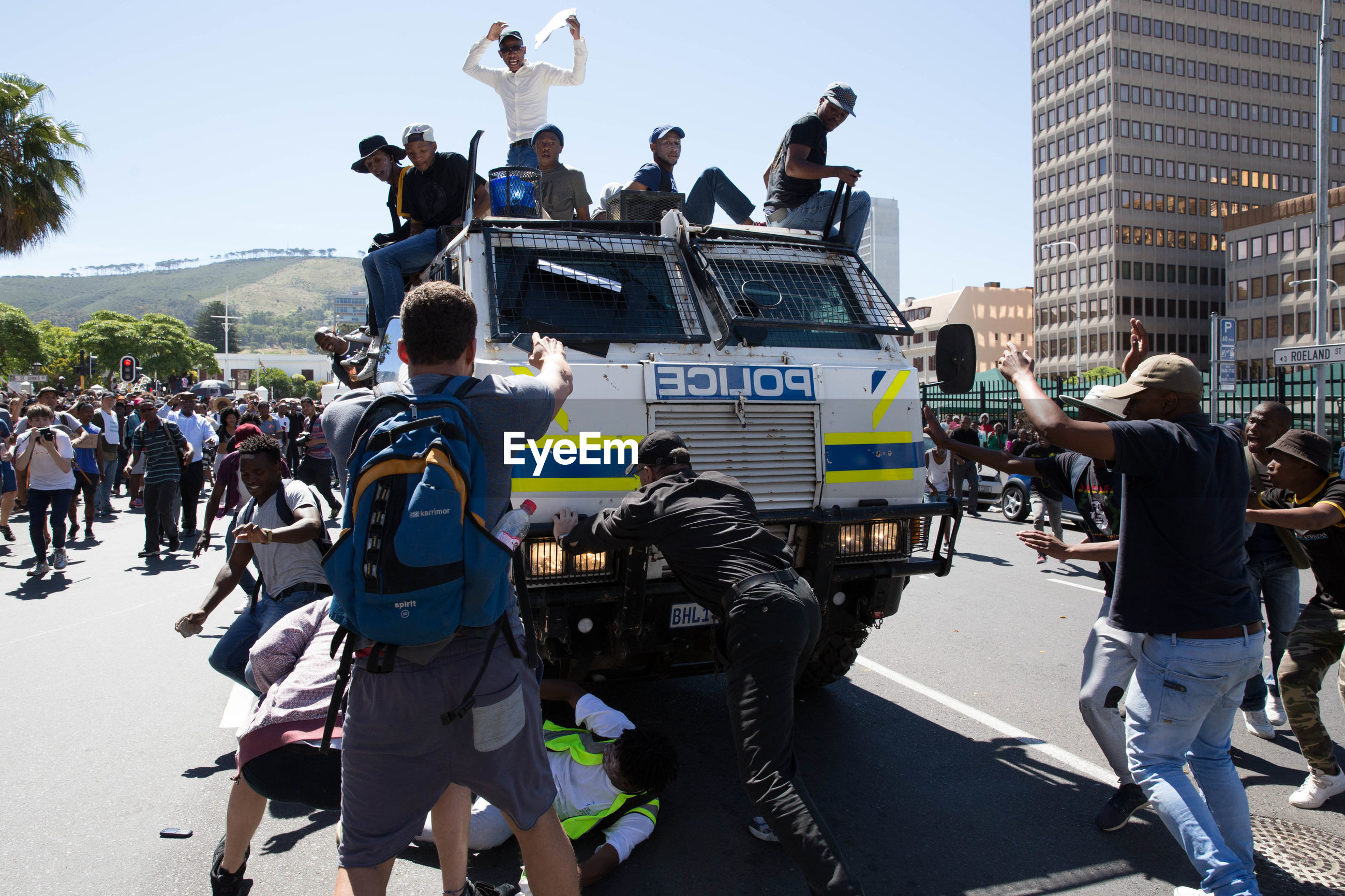men, police force, real people, building exterior, large group of people, authority, architecture, protestor, police uniform, justice - concept, built structure, day, outdoors, togetherness, shield, riot, city, sky, police station, people