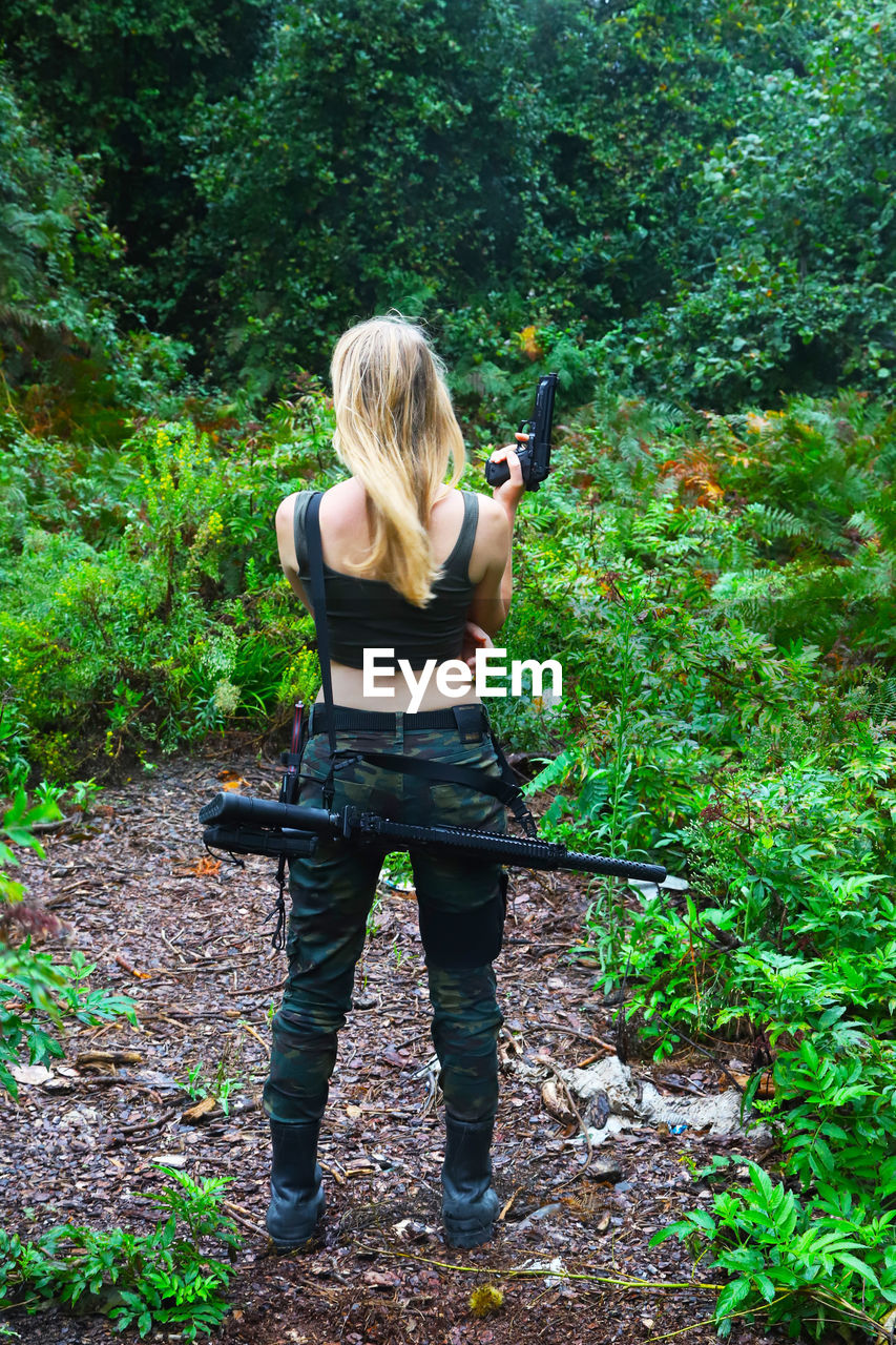 Woman with rifle standing in forest