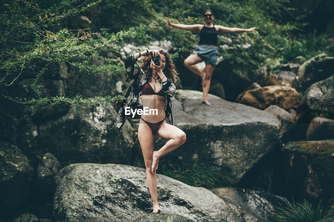 Woman photographing while doing yoga with friend in forest