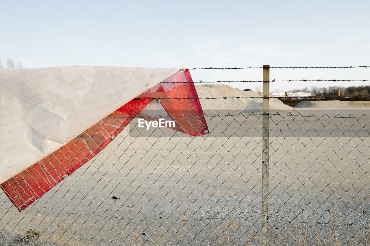 sky, day, safety, fence, no people, barrier, boundary, security, protection, architecture, nature, built structure, red, outdoors, chainlink fence, water, communication, sign, flag