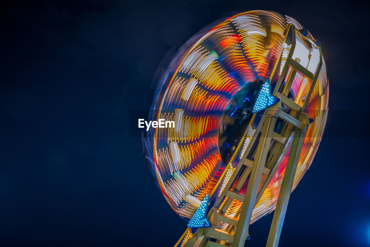 amusement park ride, amusement park, arts culture and entertainment, ferris wheel, illuminated, night, low angle view, sky, multi colored, no people, spinning, nature, blue, motion, outdoors, geometric shape, blurred motion, copy space, shape, leisure activity, fairground