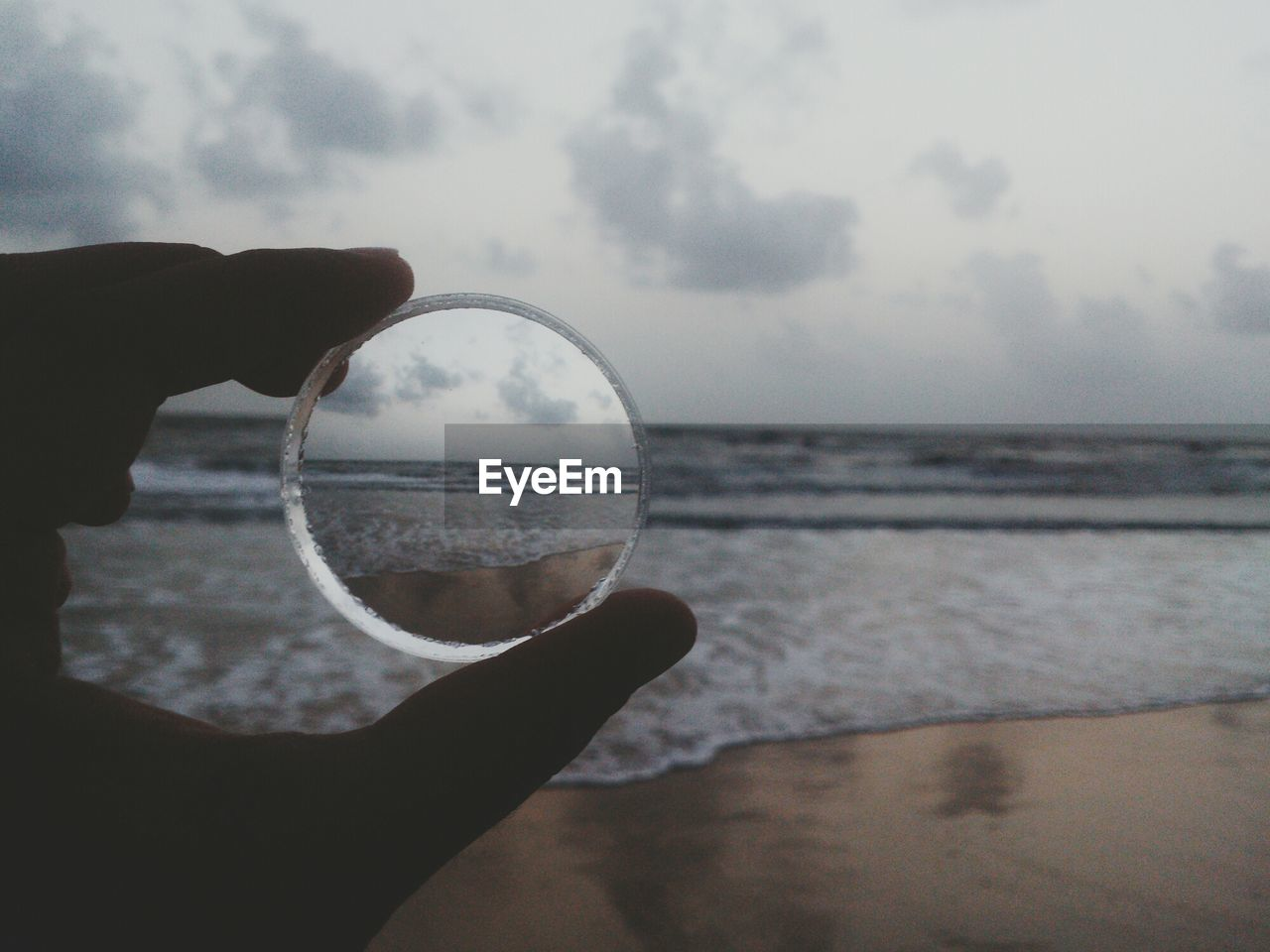 Close-up of hand holding lens at calm beach against sky