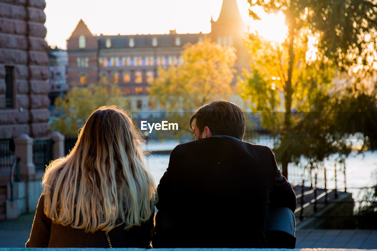 Rear View Of Couple Sitting In City During Sunset