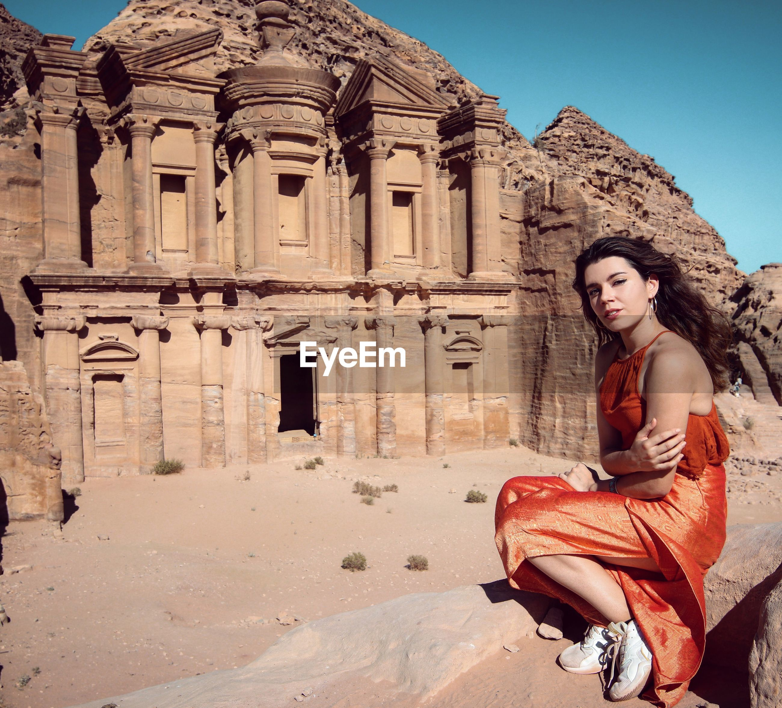 Portrait of beautiful young woman sitting against historic building