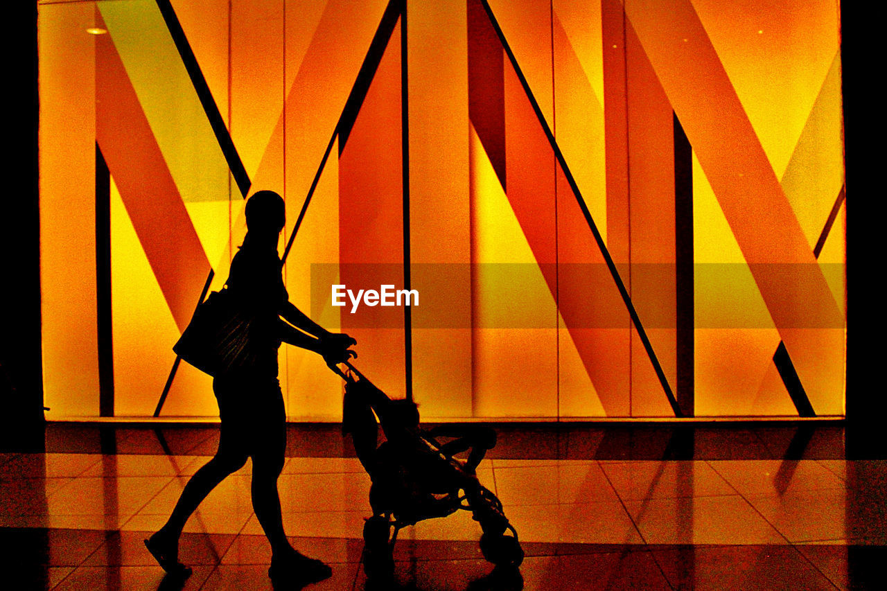 Silhouette mother with baby carriage walking in mall