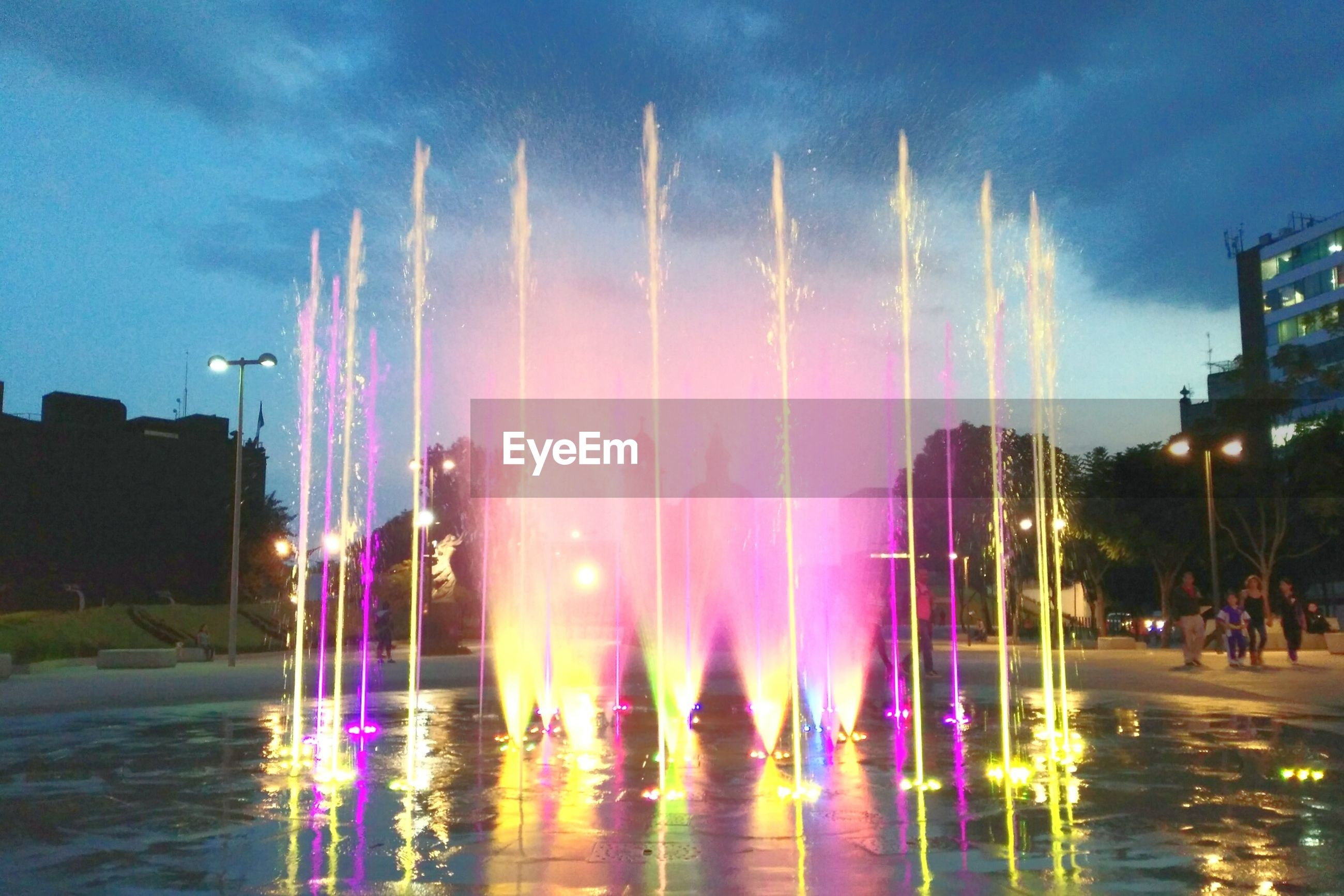 water, building exterior, fountain, built structure, illuminated, sky, architecture, motion, long exposure, city, lifestyles, large group of people, spraying, waterfront, person, night, leisure activity, men, enjoyment