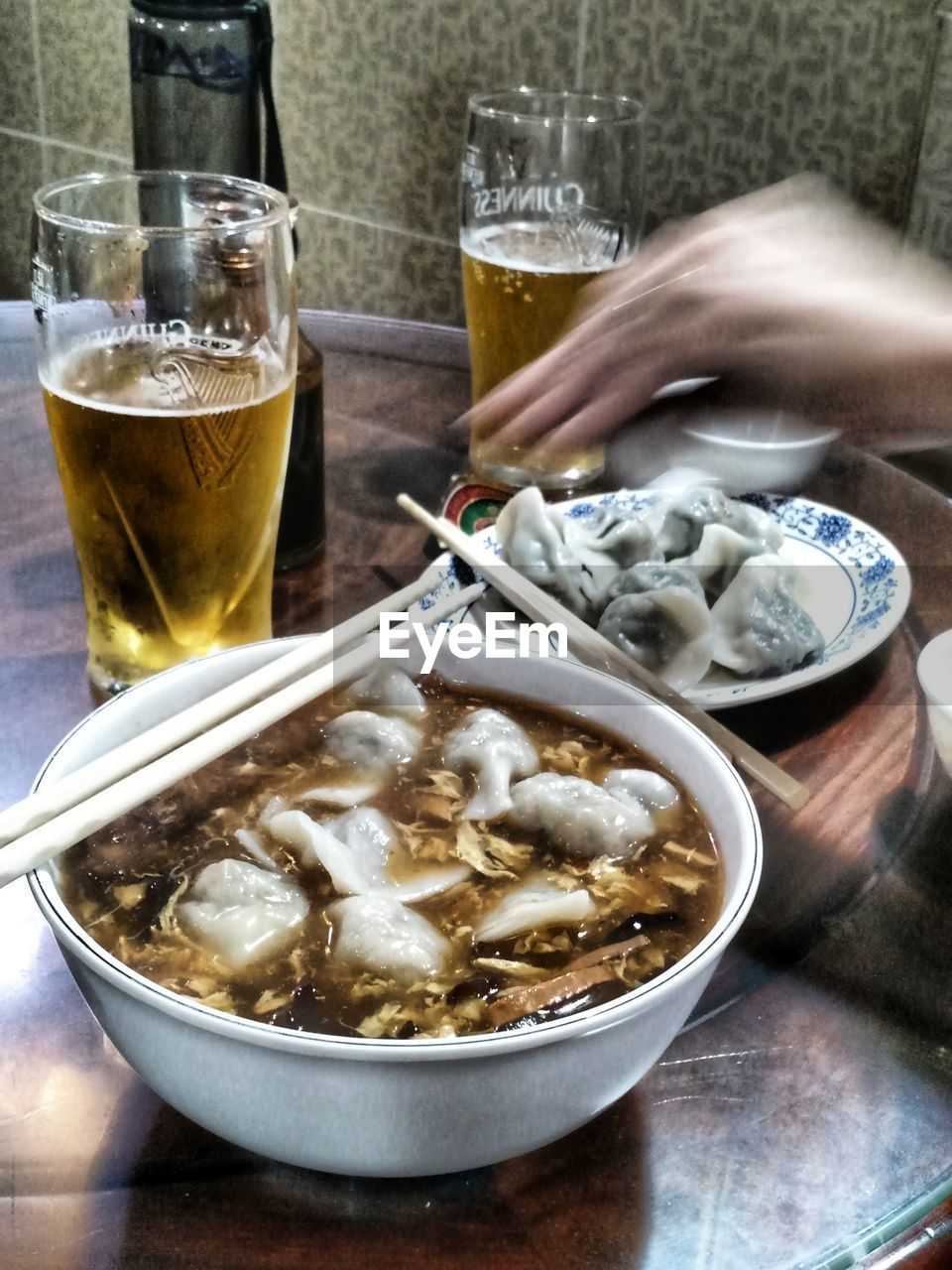 food and drink, glass, drinking glass, drink, table, food, beer, household equipment, refreshment, alcohol, freshness, bowl, beer - alcohol, indoors, beer glass, ready-to-eat, serving size, still life, human hand