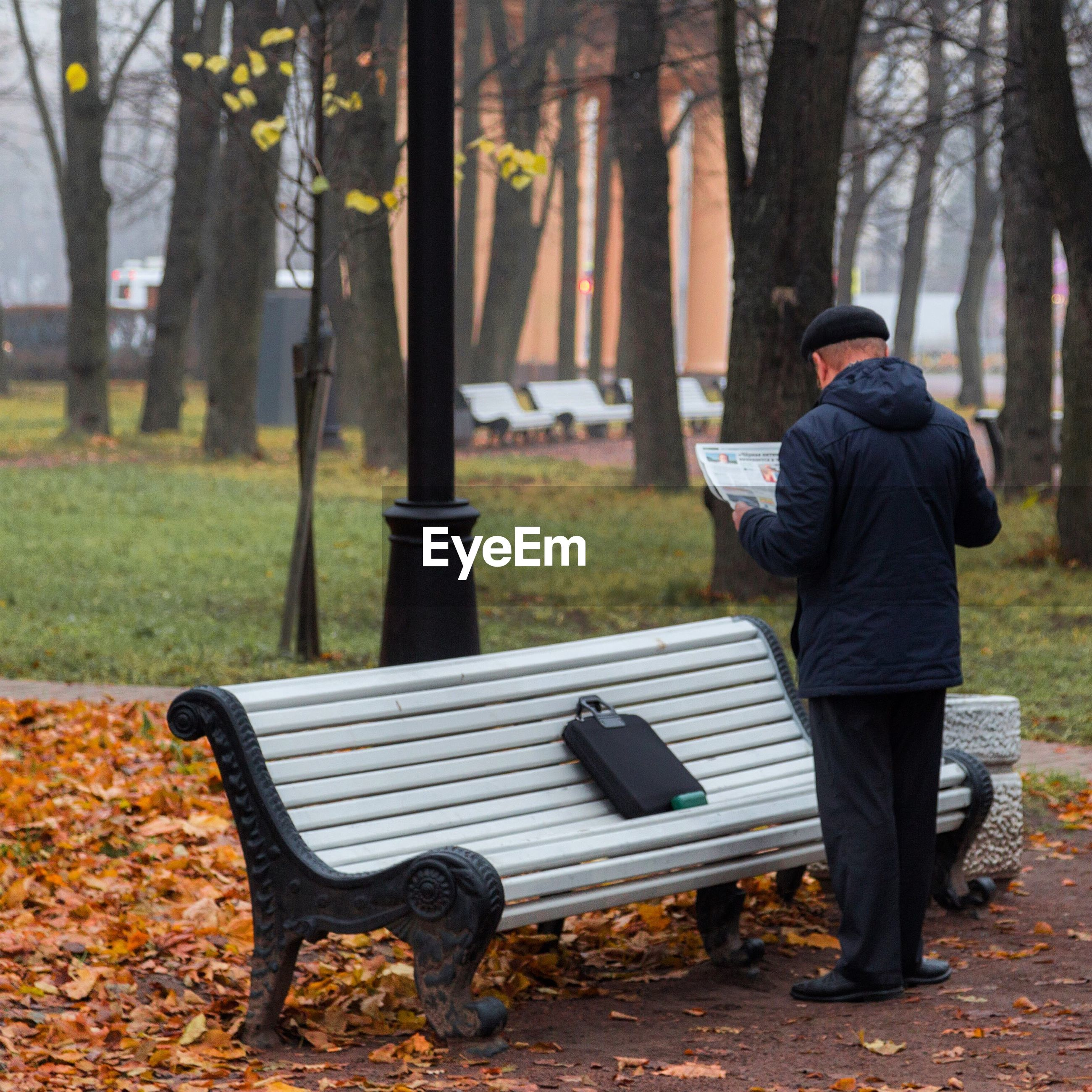 Full length rear view of man reading newspaper by bench in park during autumn