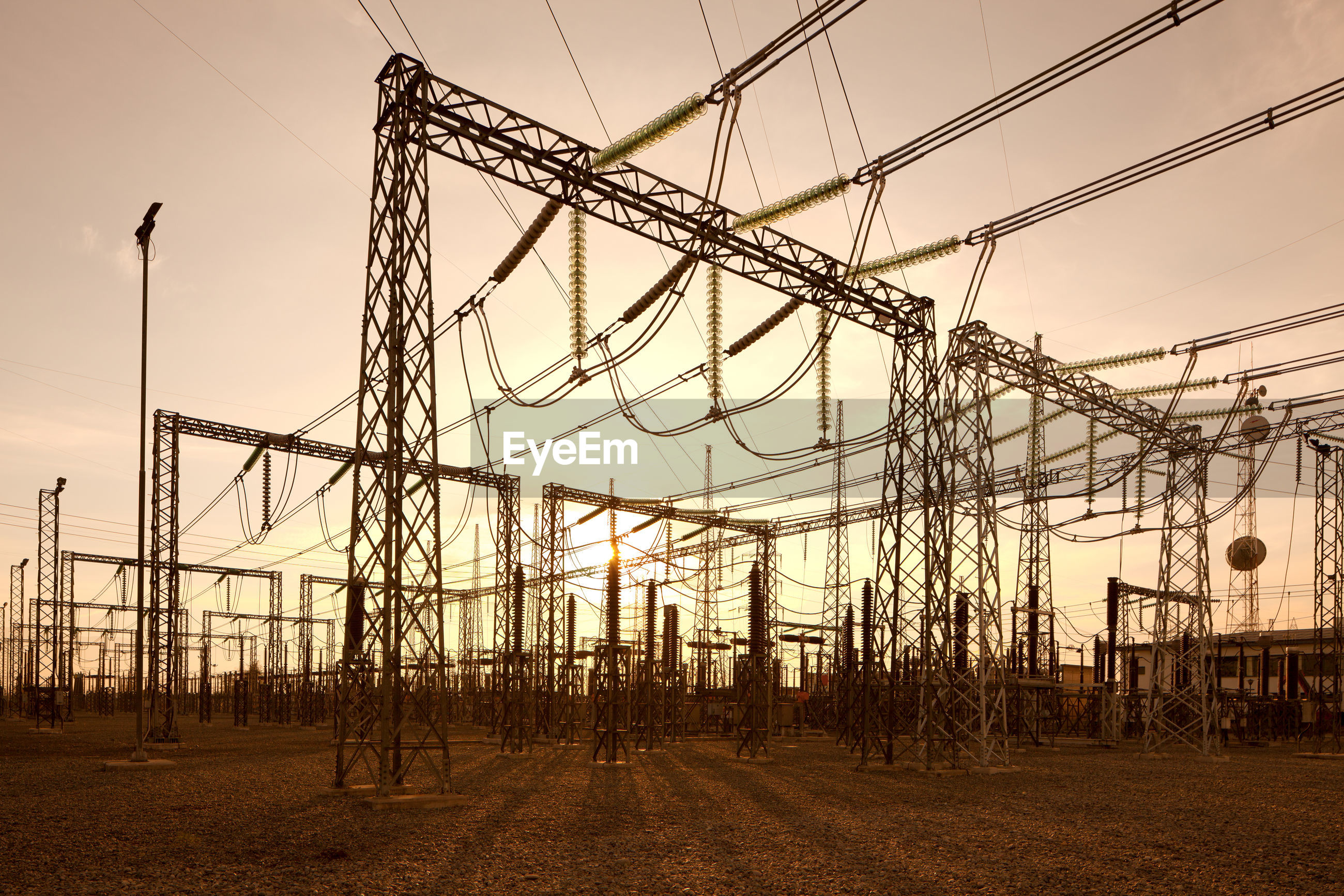 Low angle view of electric power substation during sunset
