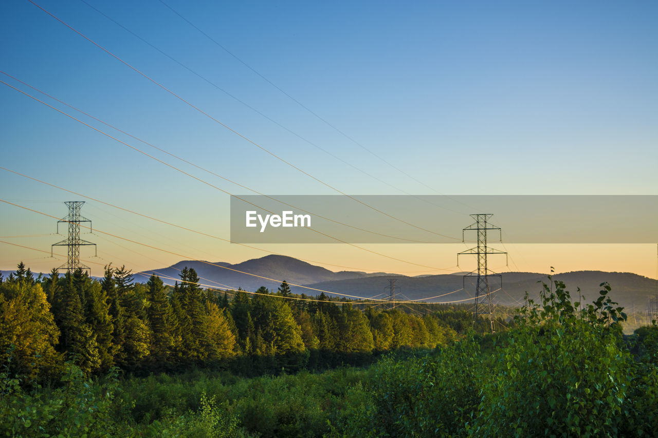 ELECTRICITY PYLONS ON LAND AGAINST CLEAR SKY DURING SUNSET