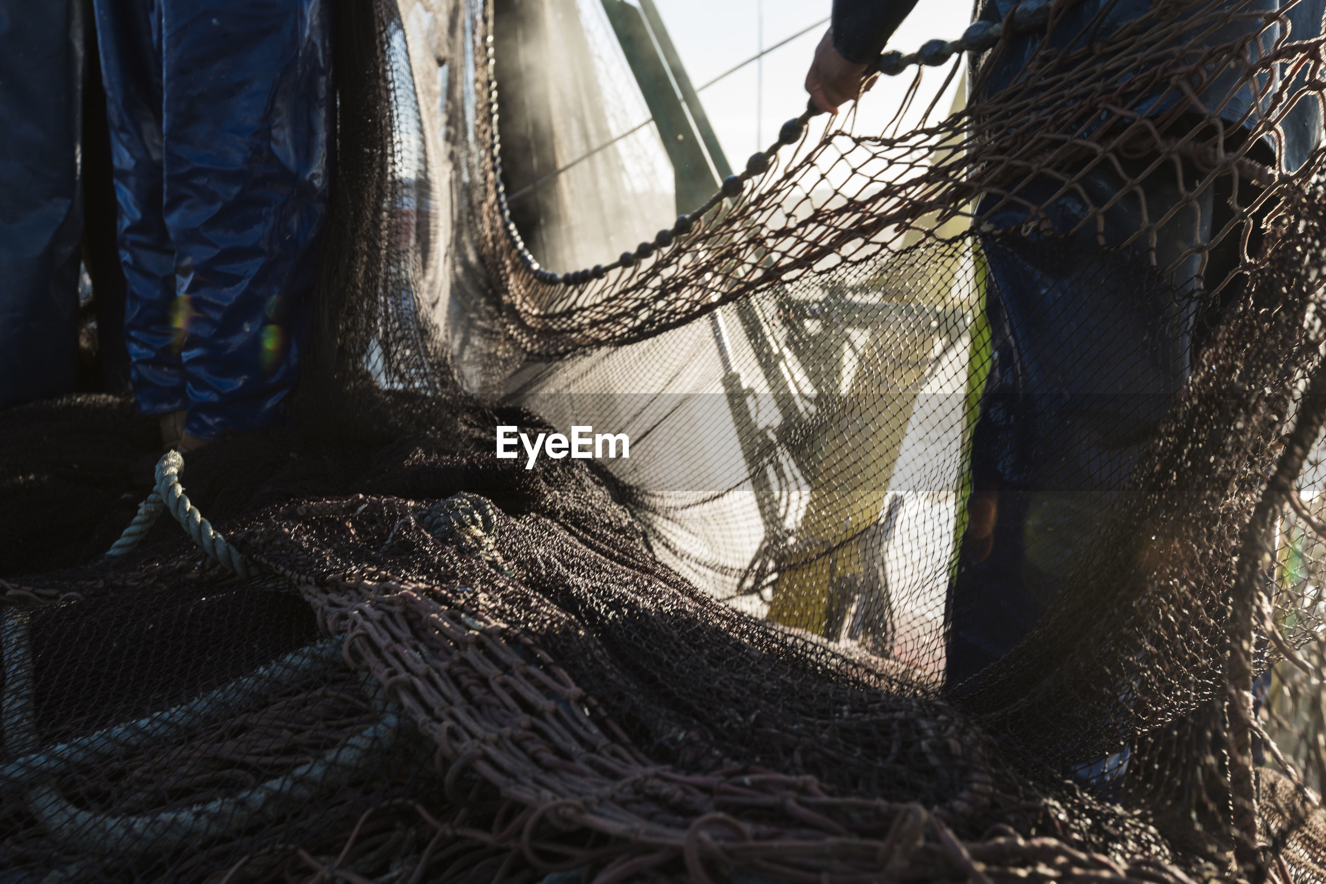 Low section of fishermen standing by fishing net