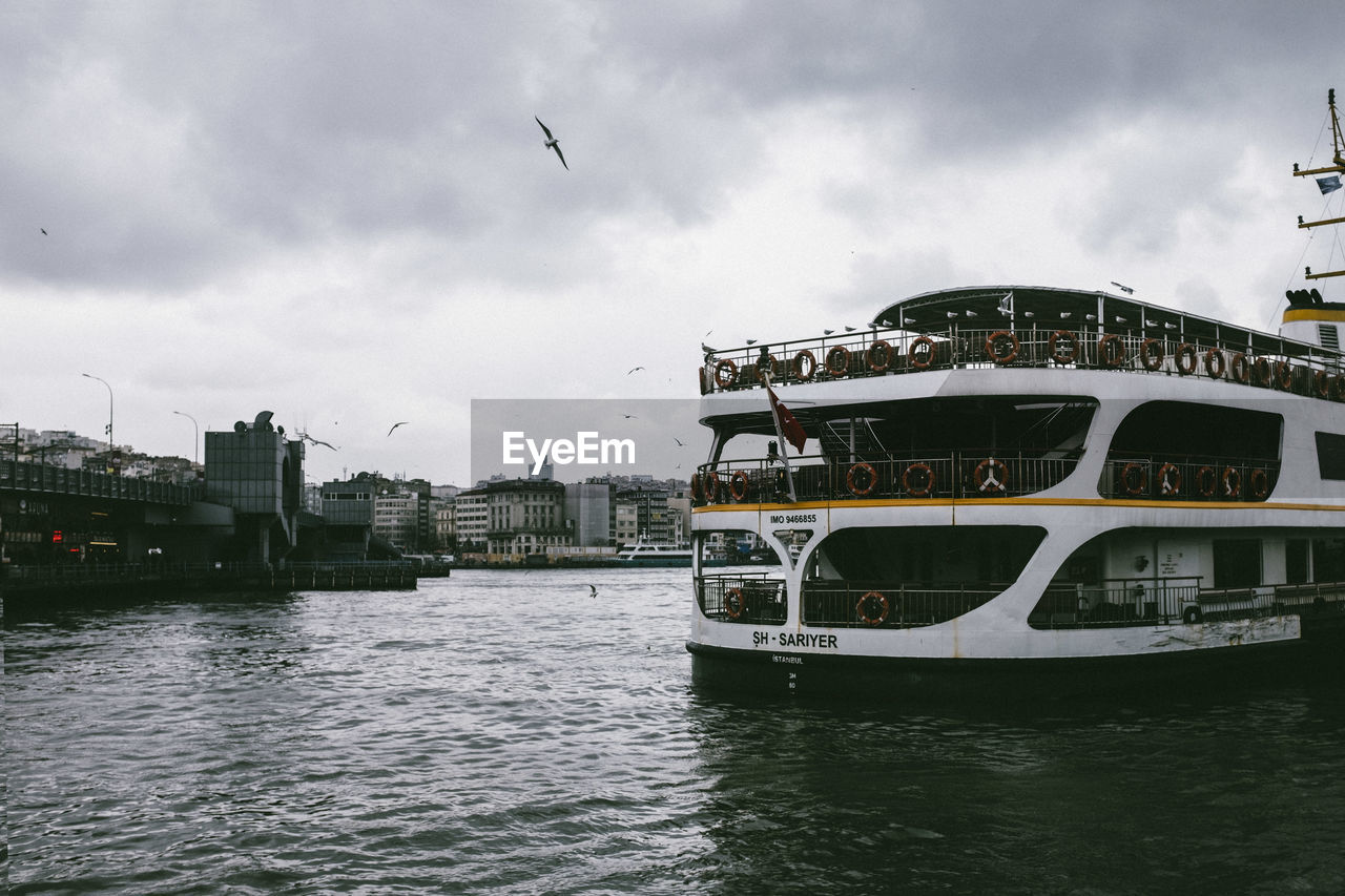 cloud - sky, water, architecture, building exterior, built structure, sky, waterfront, river, city, nautical vessel, nature, transportation, mode of transportation, no people, flying, bird, vertebrate, animal, animal themes, outdoors, passenger craft