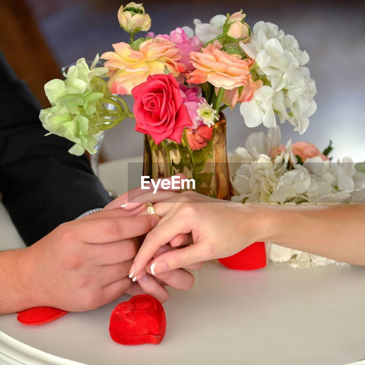 Close-up of groom wearing wedding ring to bride