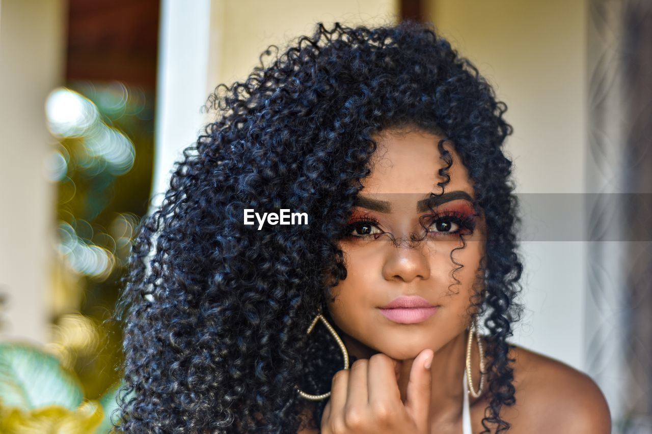 headshot, curly hair, one person, portrait, hairstyle, young adult, front view, hair, lifestyles, real people, young women, adult, black hair, leisure activity, women, indoors, looking at camera, looking, focus on foreground, beautiful woman, contemplation, frizzy