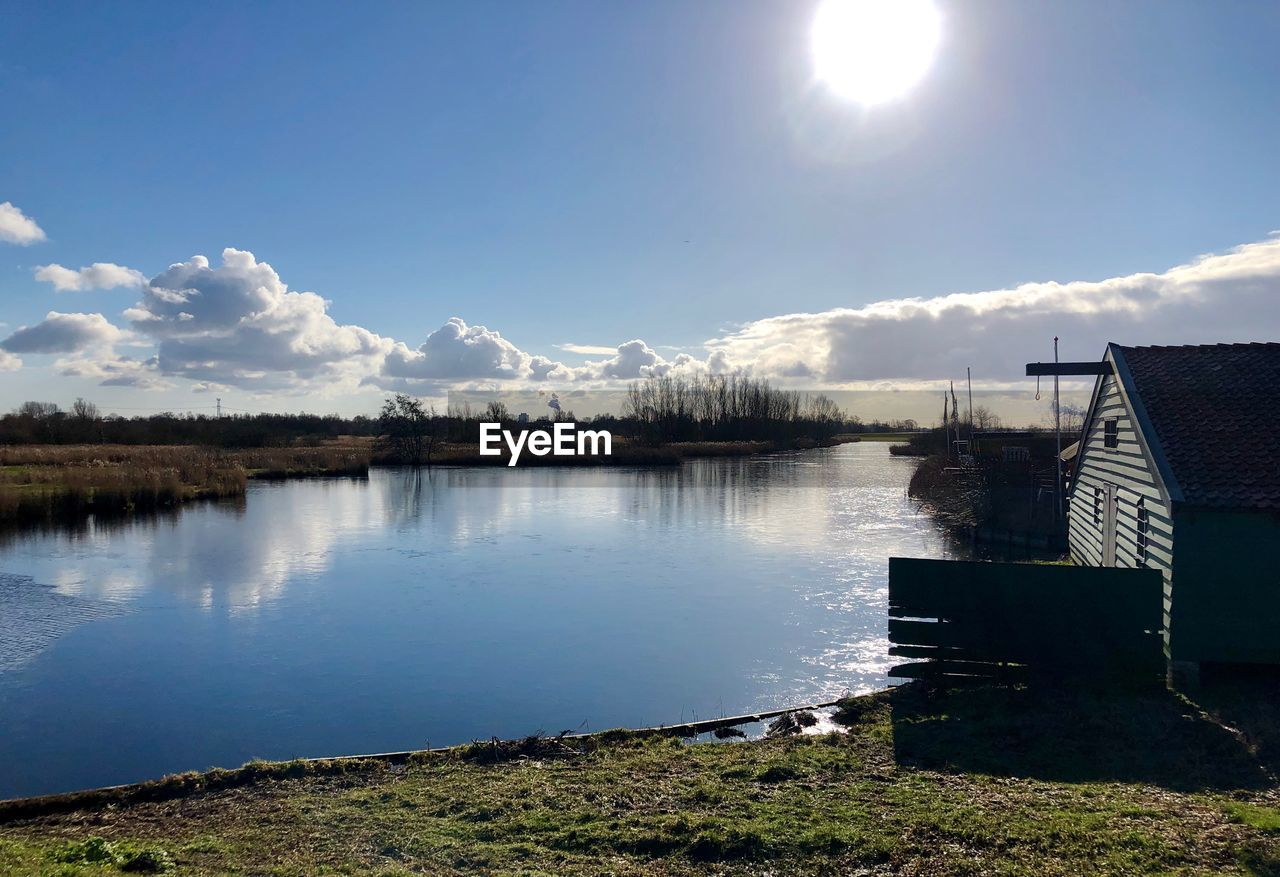 water, sky, lake, nature, reflection, tranquility, cloud - sky, sunlight, tranquil scene, architecture, scenics - nature, built structure, beauty in nature, no people, day, outdoors, non-urban scene, building exterior, idyllic