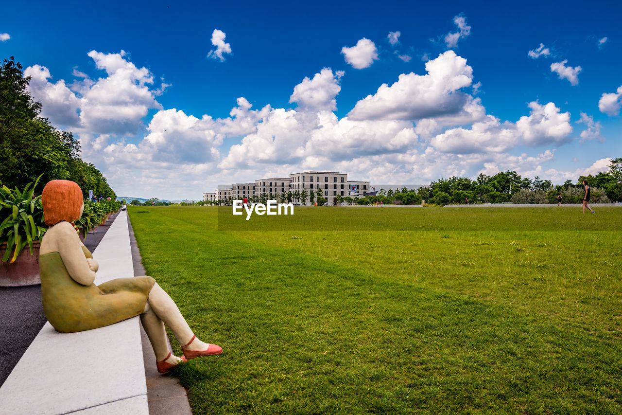 plant, sky, cloud - sky, grass, architecture, nature, day, tree, building exterior, green color, built structure, land, field, growth, city, park, outdoors, lawn, people, beauty in nature