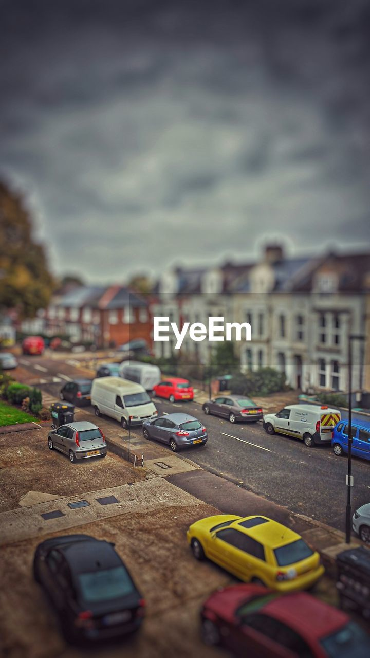 Tilt-shift image of cars on city street against sky