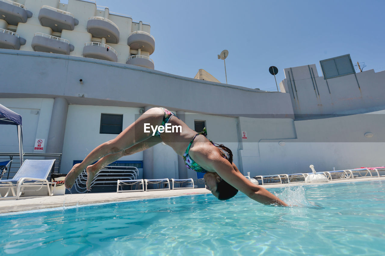 LOW ANGLE VIEW OF MAN JUMPING IN SWIMMING POOL AGAINST SKY