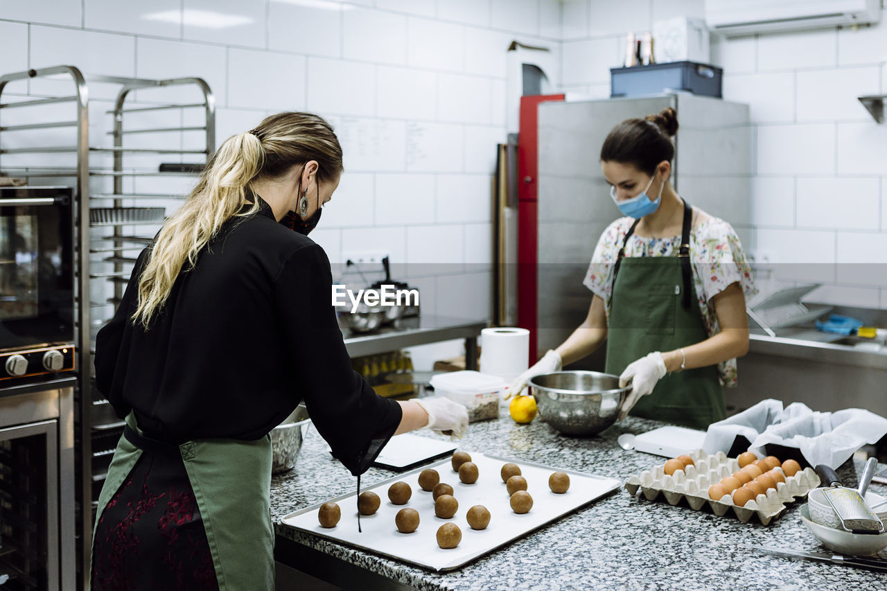 YOUNG WOMAN STANDING WITH PEOPLE IN KITCHEN