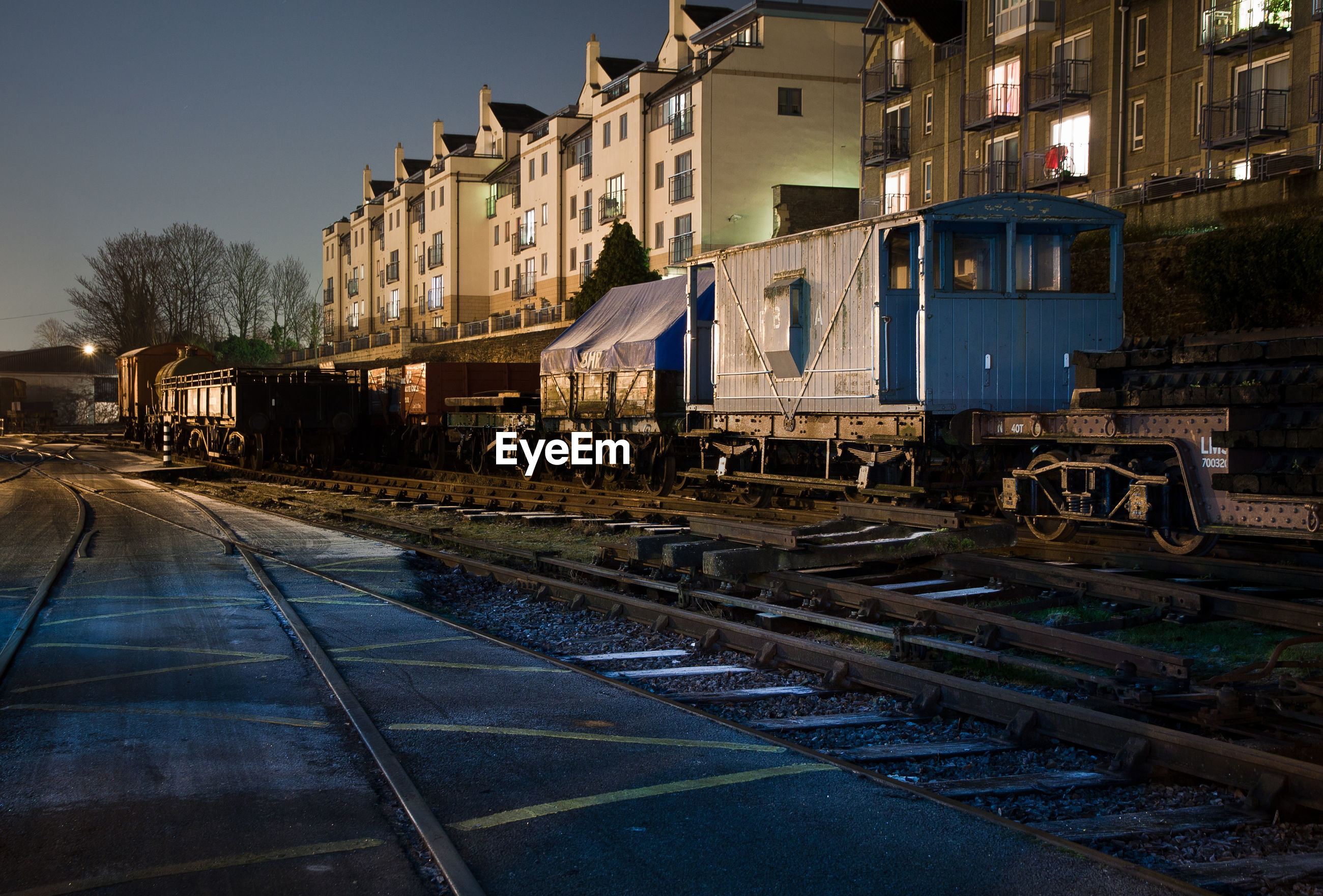 Freight trains on railroad tracks by buildings at night