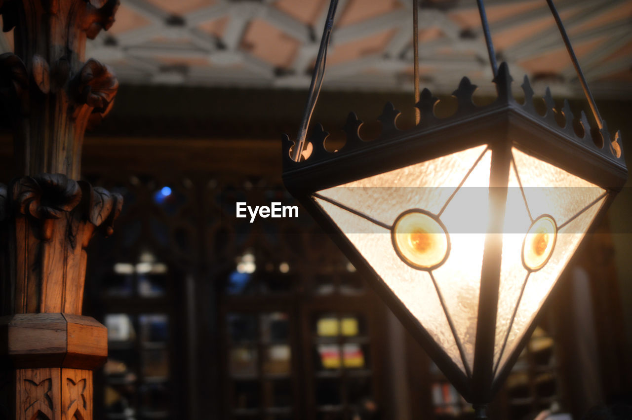 focus on foreground, hanging, illuminated, lighting equipment, no people, indoors, close-up, day