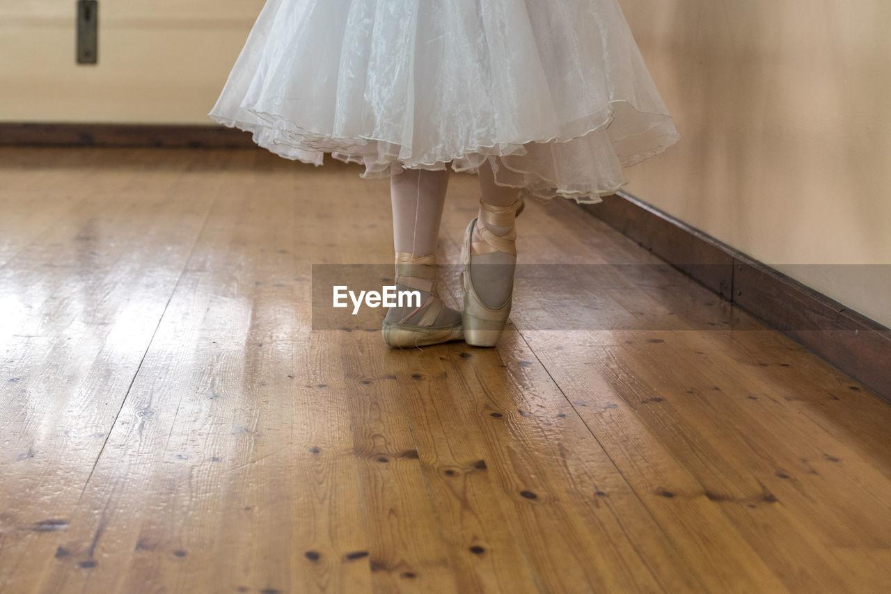 Low Section Of Ballet Dancer On Hardwood Floor