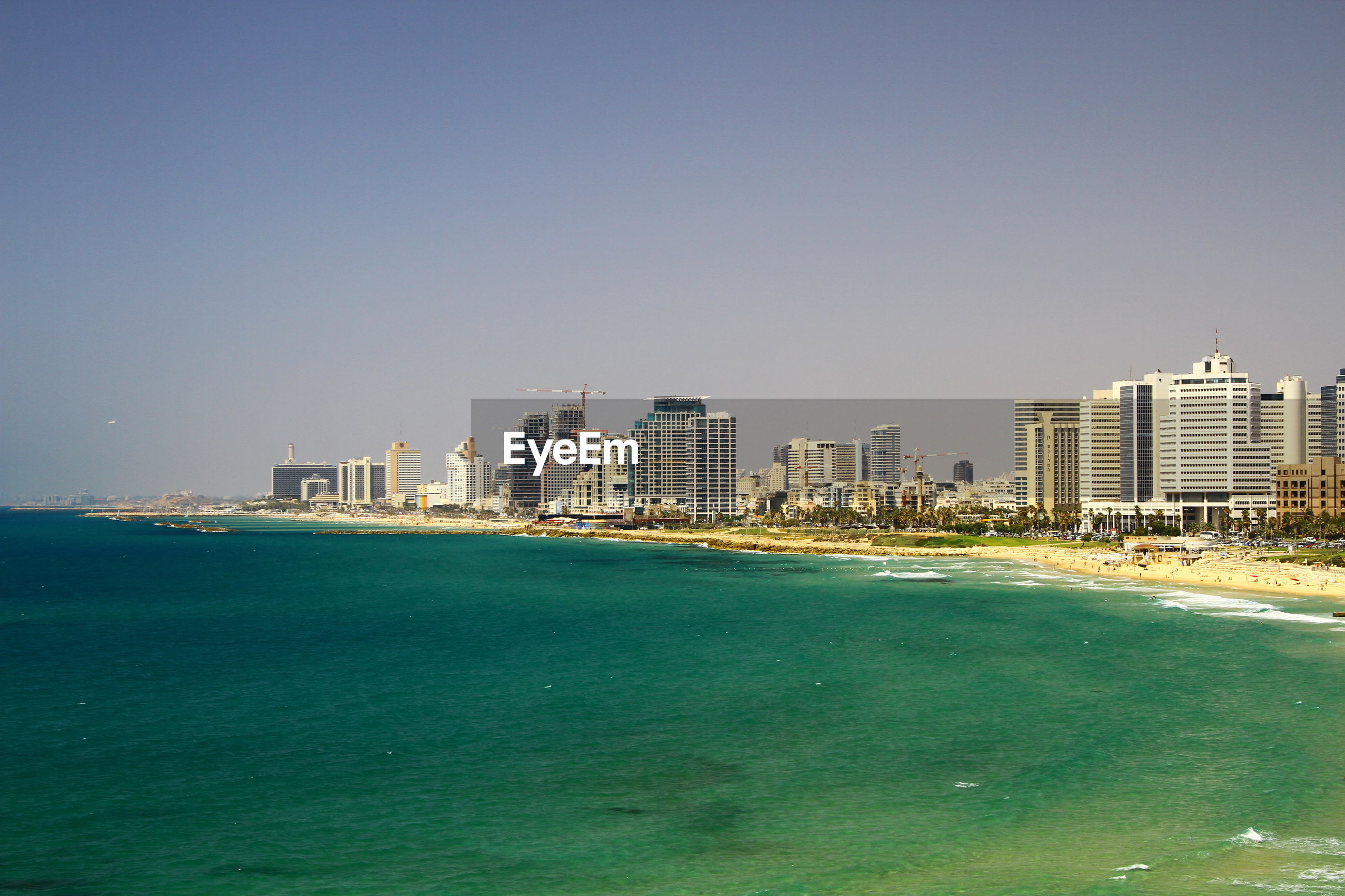 SCENIC VIEW OF SEA AND CITY AGAINST CLEAR SKY