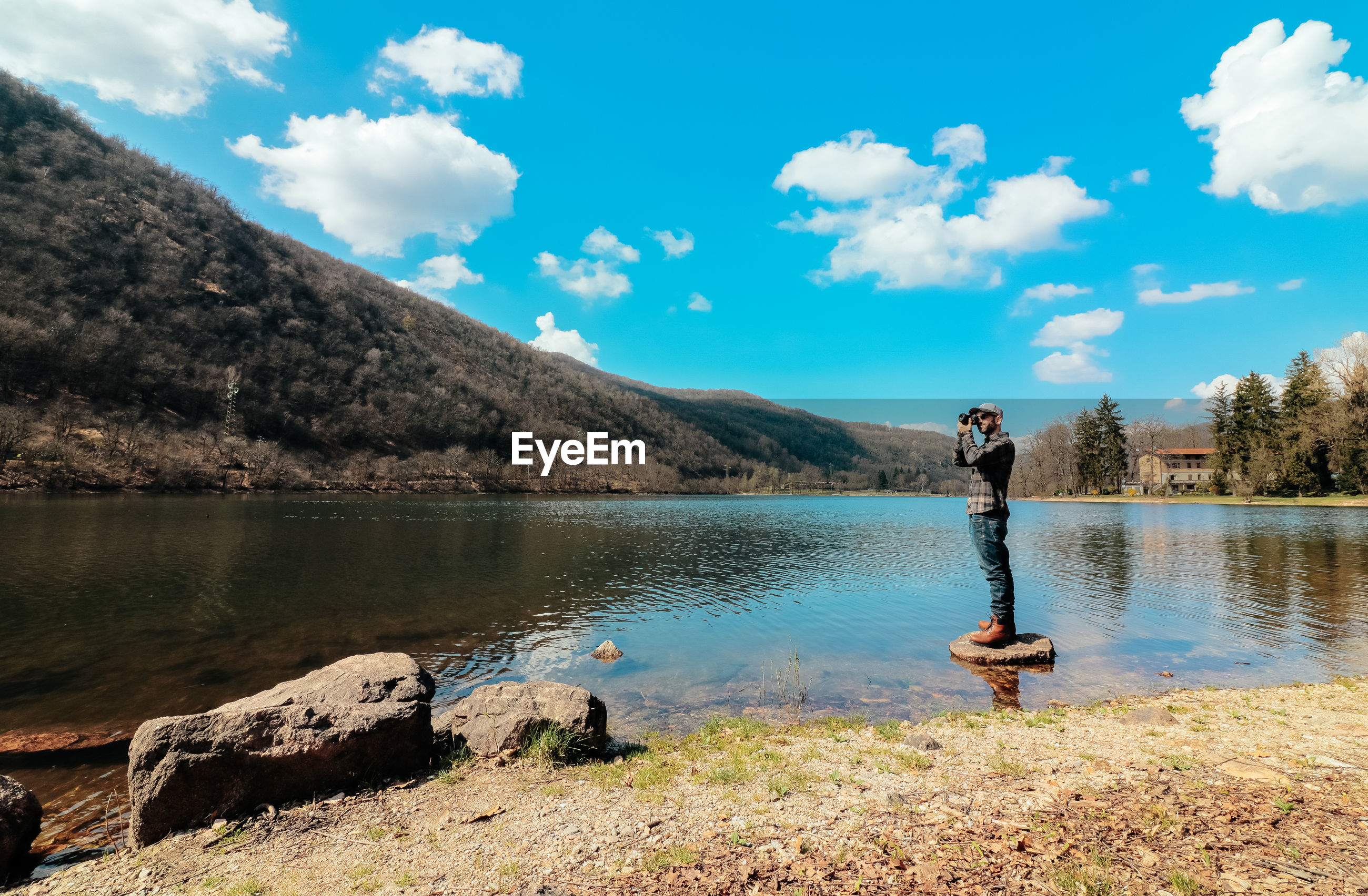 MAN STANDING BY LAKE AGAINST MOUNTAIN