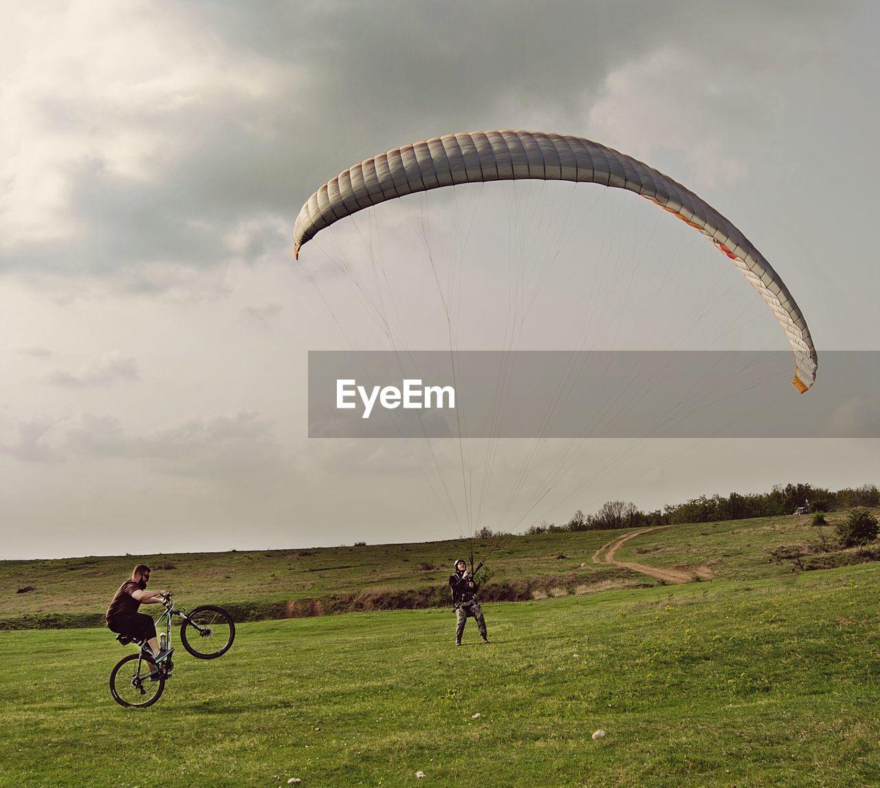 Bmx biker and paraglider on field