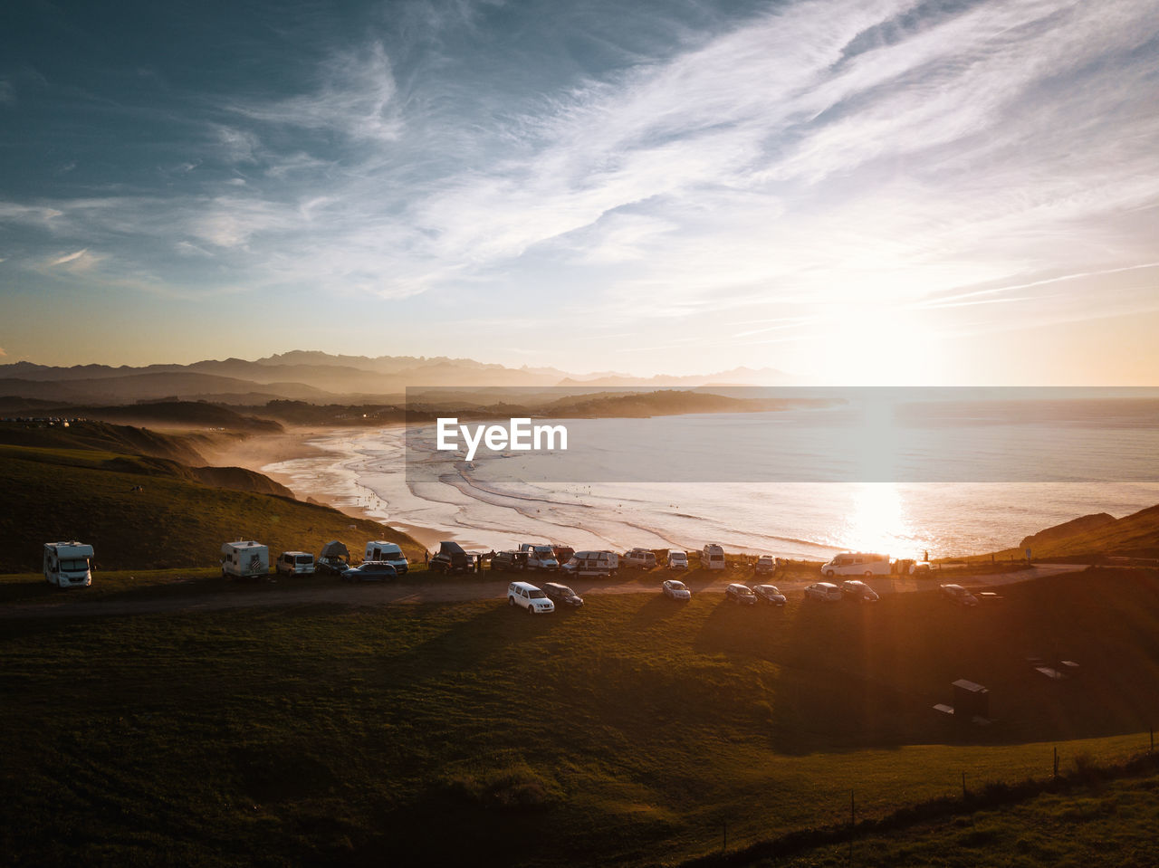 sky, scenics - nature, beauty in nature, cloud - sky, tranquil scene, sunset, tranquility, nature, environment, land, sunlight, sun, landscape, non-urban scene, mountain, no people, sunbeam, idyllic, field, land vehicle, lens flare, outdoors, bright