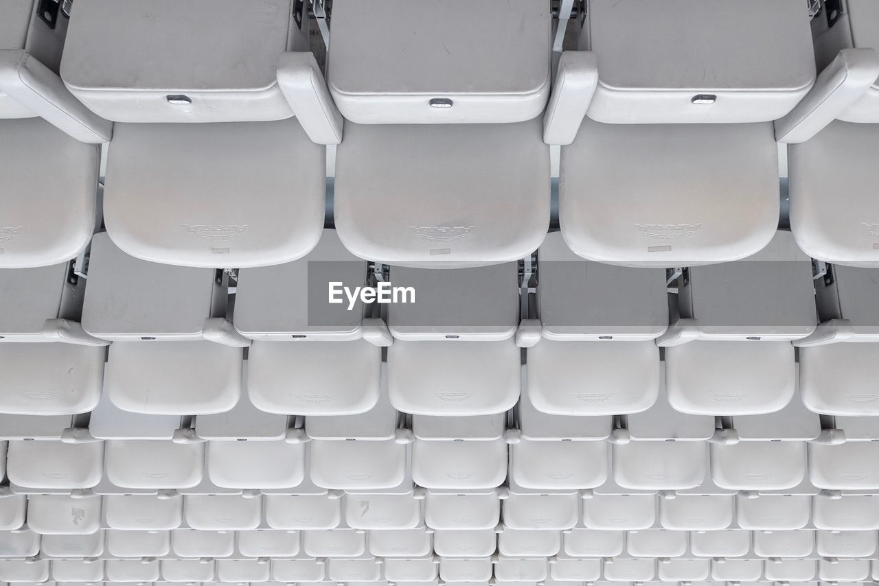 in a row, backgrounds, full frame, white color, side by side, repetition, seat, no people, empty, chair, indoors, absence, arrangement, pattern, large group of objects, order, high angle view, arts culture and entertainment, stadium