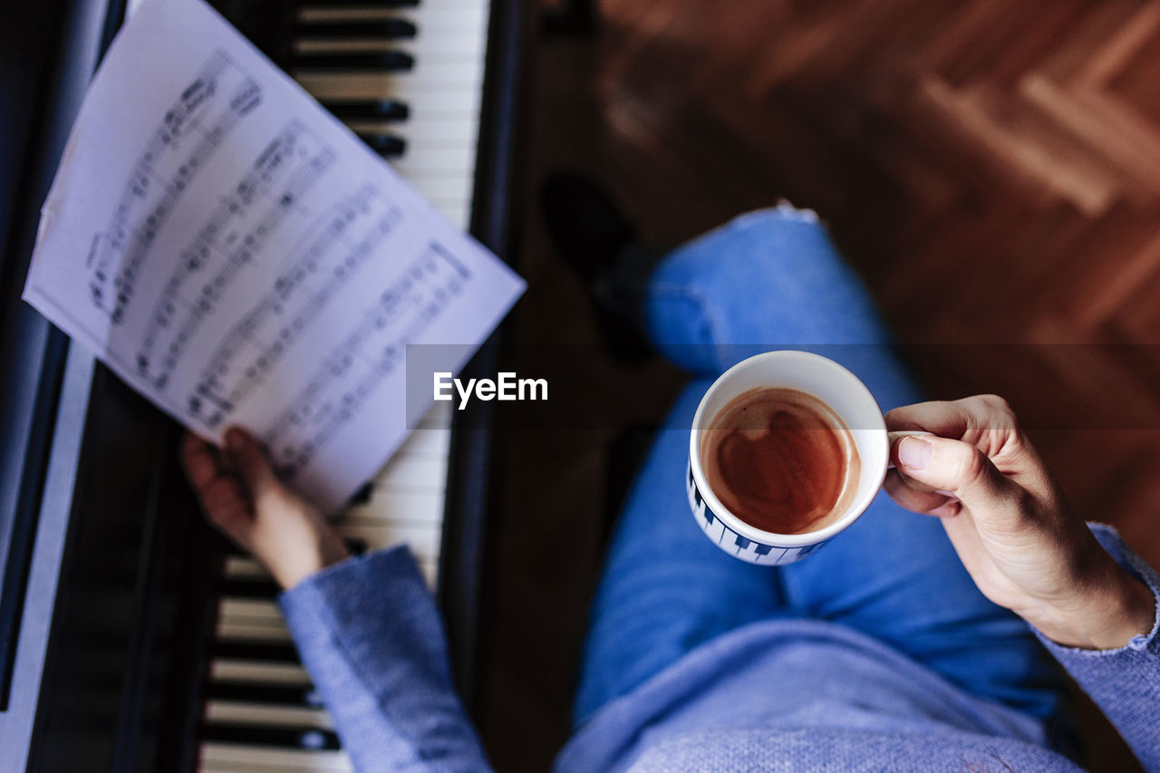 holding, cup, real people, drink, one person, coffee - drink, food and drink, coffee, refreshment, indoors, coffee cup, mug, human body part, low section, human hand, personal perspective, lifestyles, leisure activity, paper, hand, body part