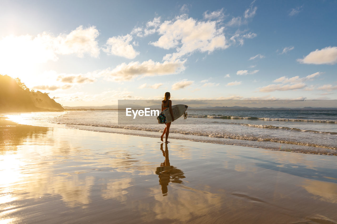 water, beach, sea, sky, one person, land, beauty in nature, real people, full length, lifestyles, leisure activity, scenics - nature, reflection, standing, non-urban scene, sand, cloud - sky, nature, horizon over water