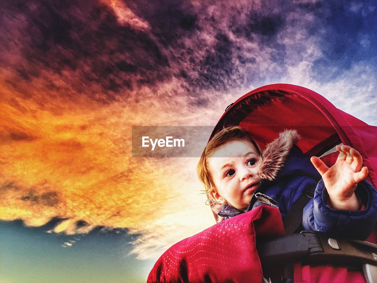 Low Angle View Of Child In Baby Carriage Against Cloudy Sky At Sunset