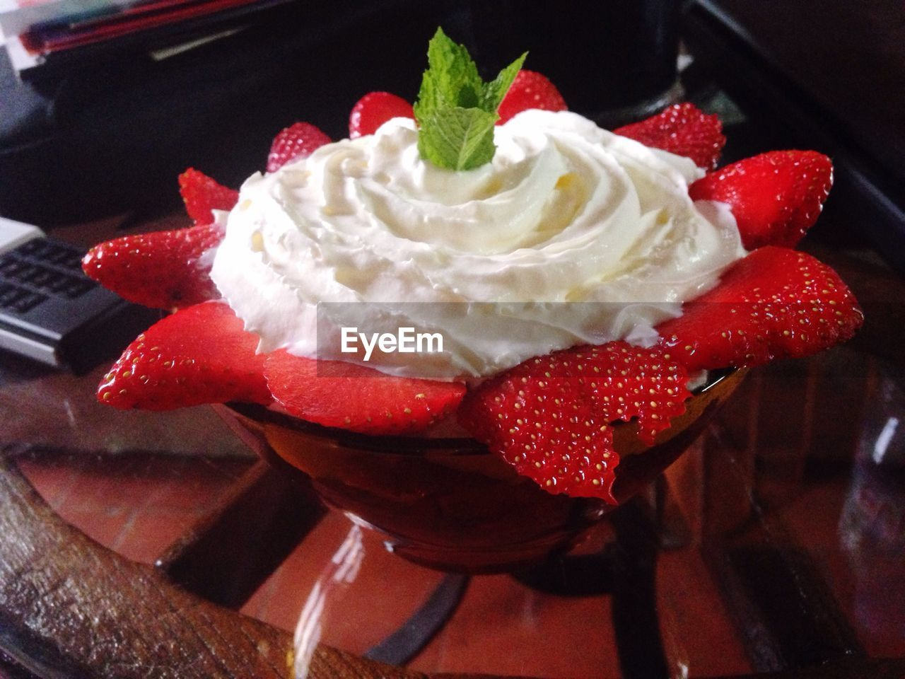 Close-up of strawberries topped with whipped cream in bowl on table