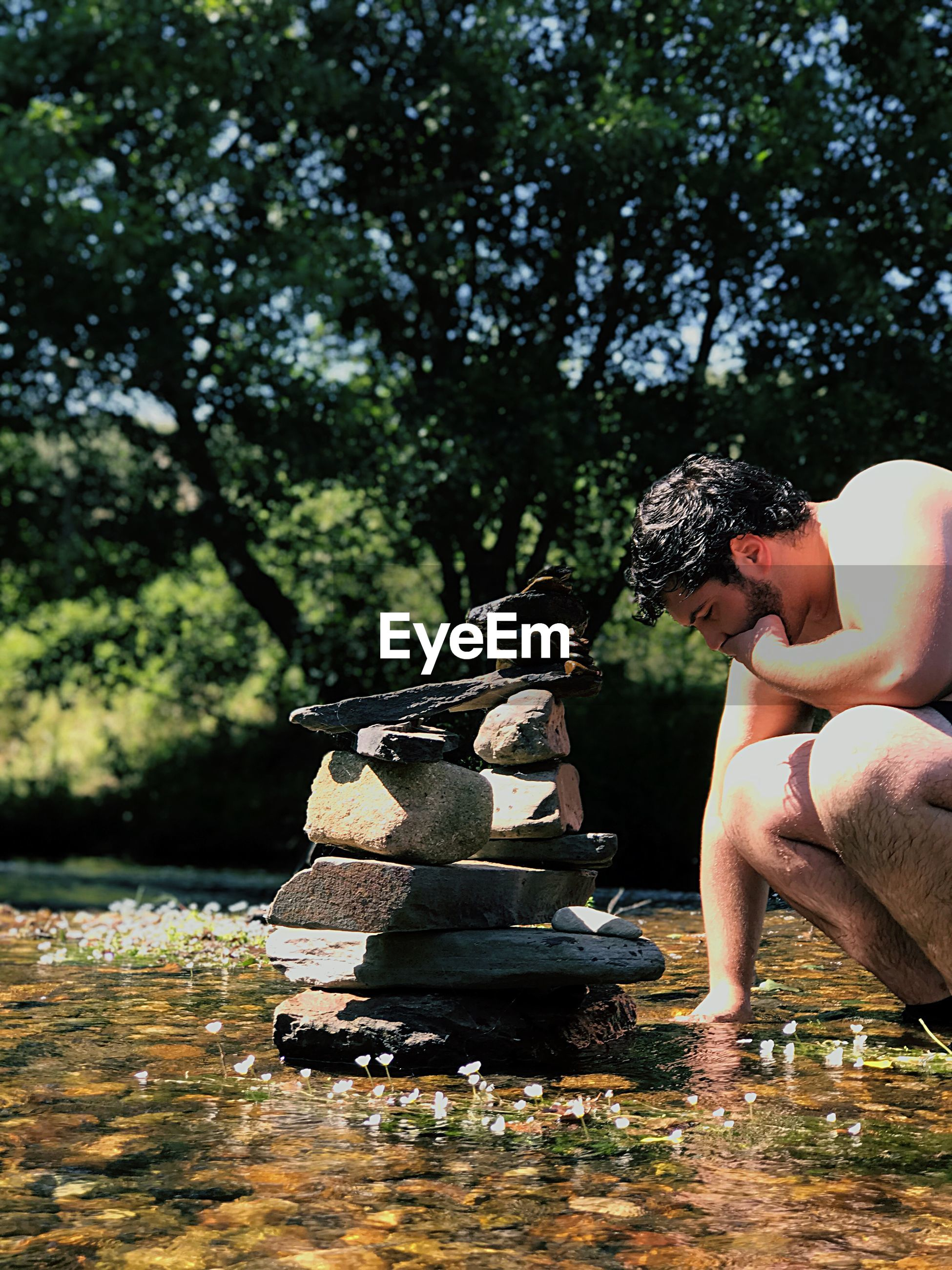 Shirtless man stacking rocks in lake