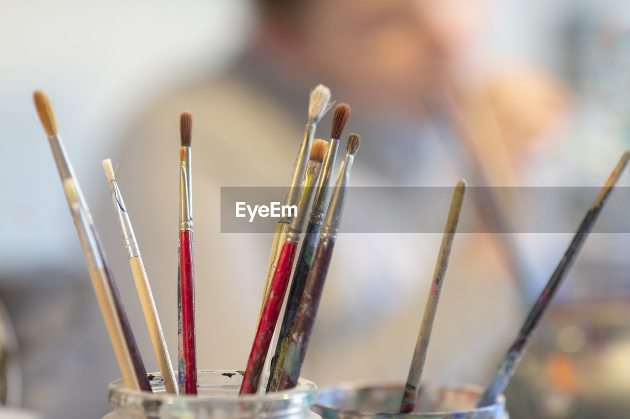 focus on foreground, brush, paintbrush, close-up, incense, art and craft, indoors, still life, belief, selective focus, no people, religion, large group of objects, spirituality, creativity, place of worship, choice, craft, art and craft equipment, stick - plant part