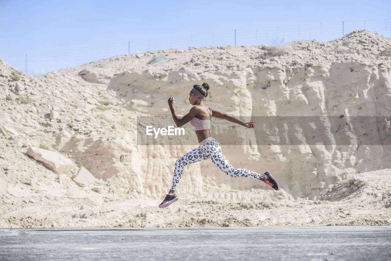 Side View Of Female Athlete Running On Road Against Rock Formation During Sunny Day