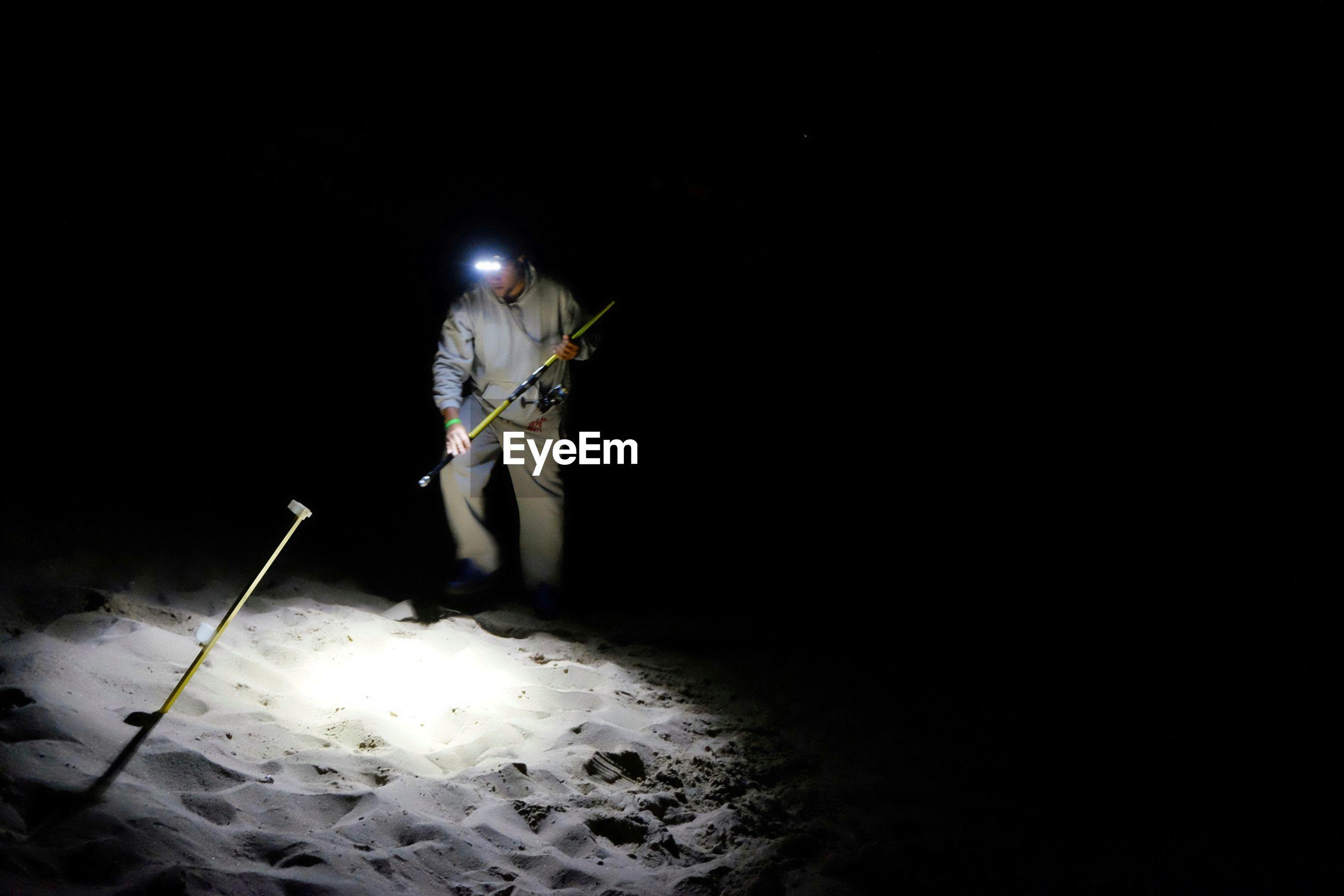 MAN HOLDING UMBRELLA WITH ILLUMINATED LIGHT